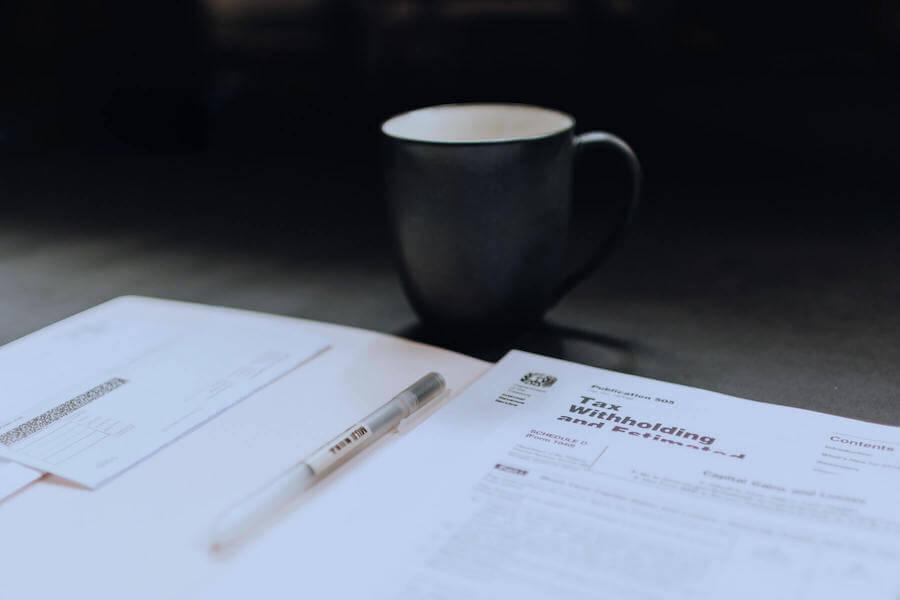 tax paperwork on table next to coffee mug travel nurse taxes