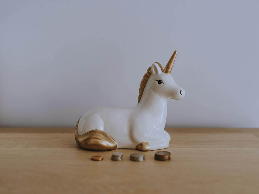 unicorn piggy bank with coin stacked in front of it budgeting for nurses
