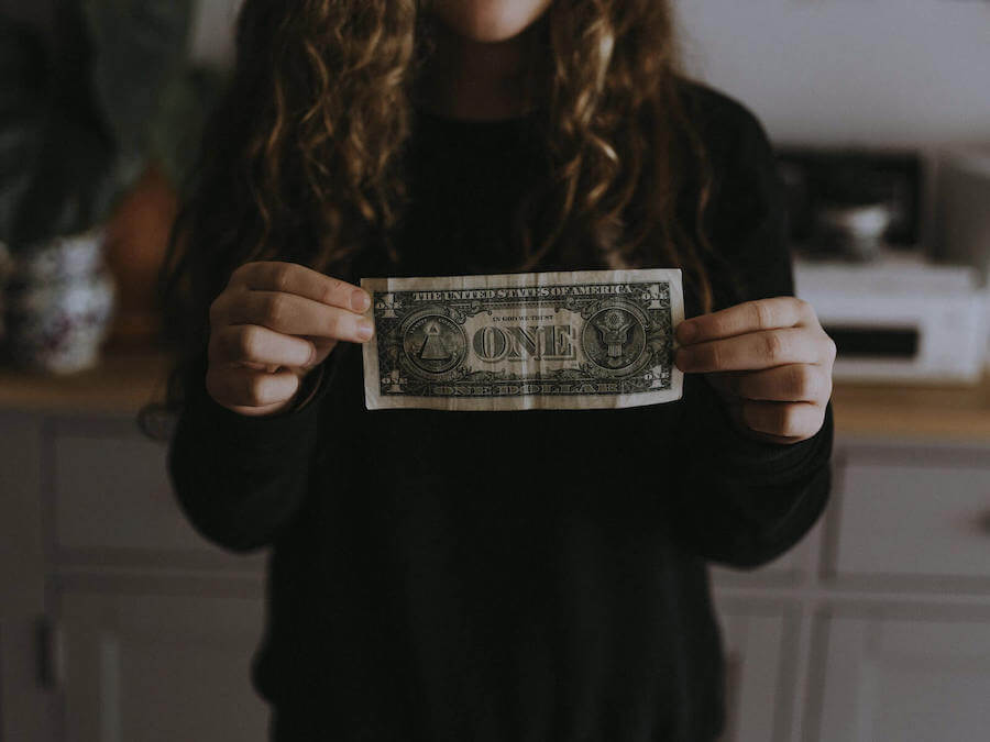 woman in black sweater holding dollar bill in front of her budgeting for nurses