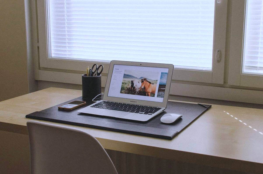 laptop on desk next to office supplies and mouse remote nursing jobs