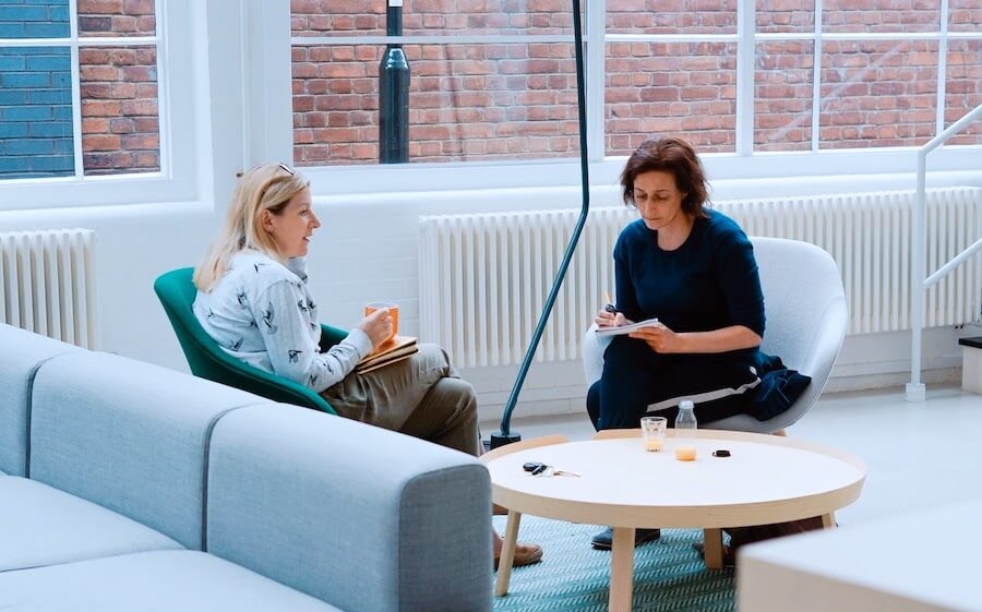 two woman sit on sofa chairs inside home studying nursing interview