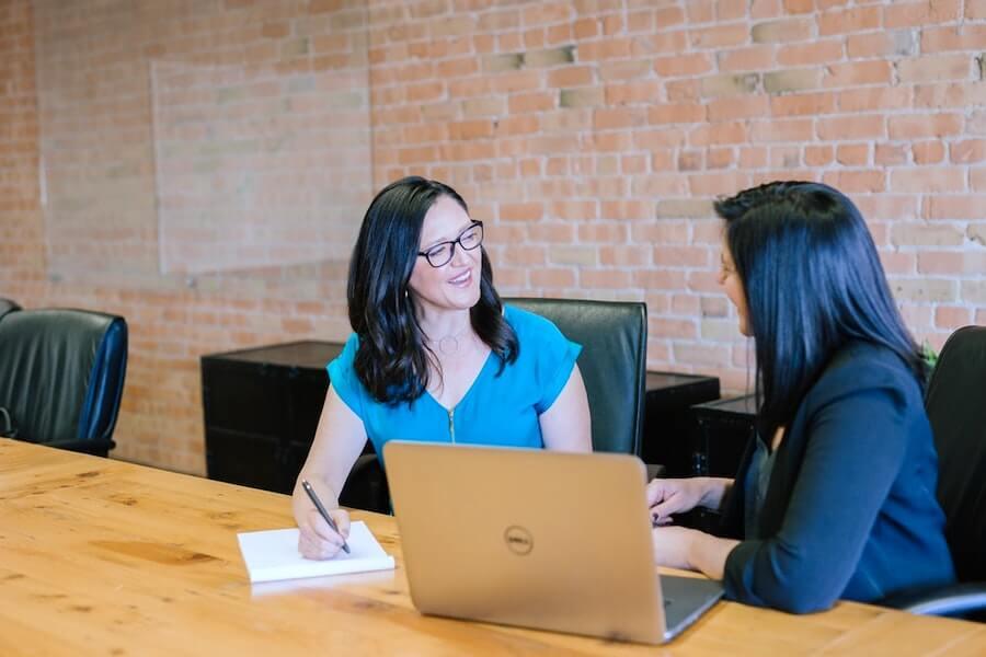 woman in teal t-shirt sitting beside woman in suit jacket nursing interview