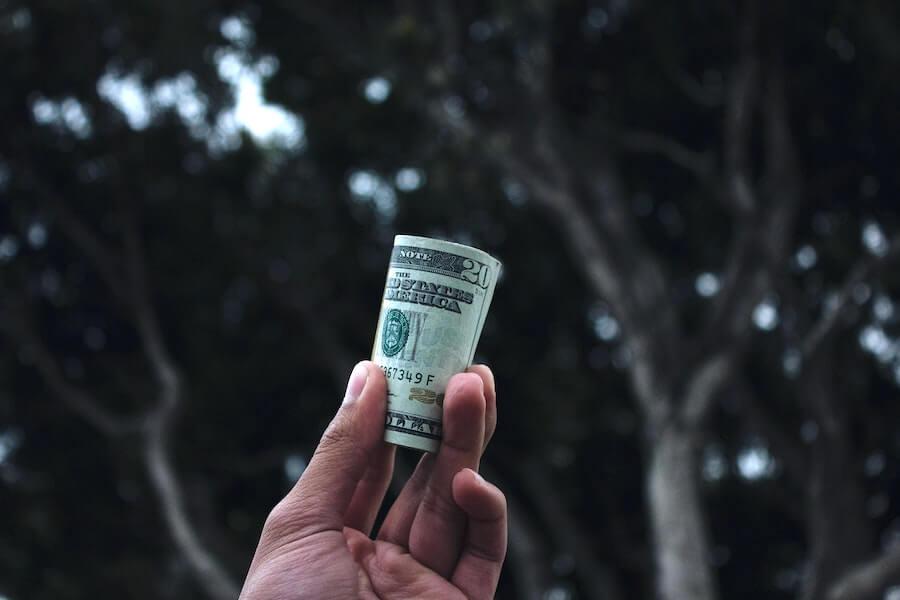 hand holding 20 dollar bills up highest paying nursing jobs 2021