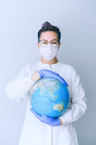 woman holding globe with mask and gloves on travel nursing jobs