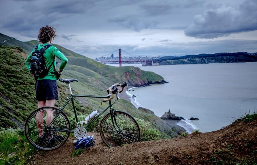 guy on bike on mountainside overlooking bay bridge travel nursing in a new city