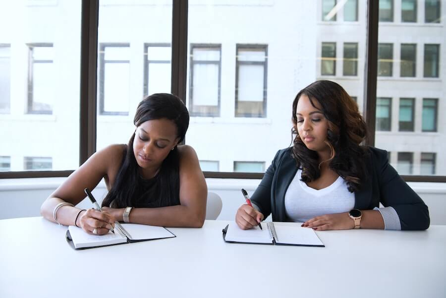 two woman taking notes next to each other on a white desk in office building during a travel nursing interview