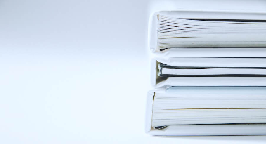 three large paper bindings are table in front of white background how to become an LPN documentation