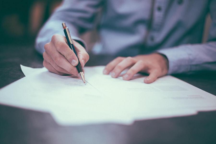 man holding pen looking at and writing on nursing resume