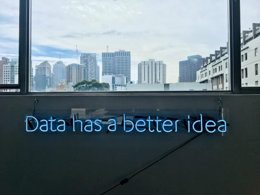 neon writing on inside of room below window looking out to skyscrapers data has a better idea informatics nurse