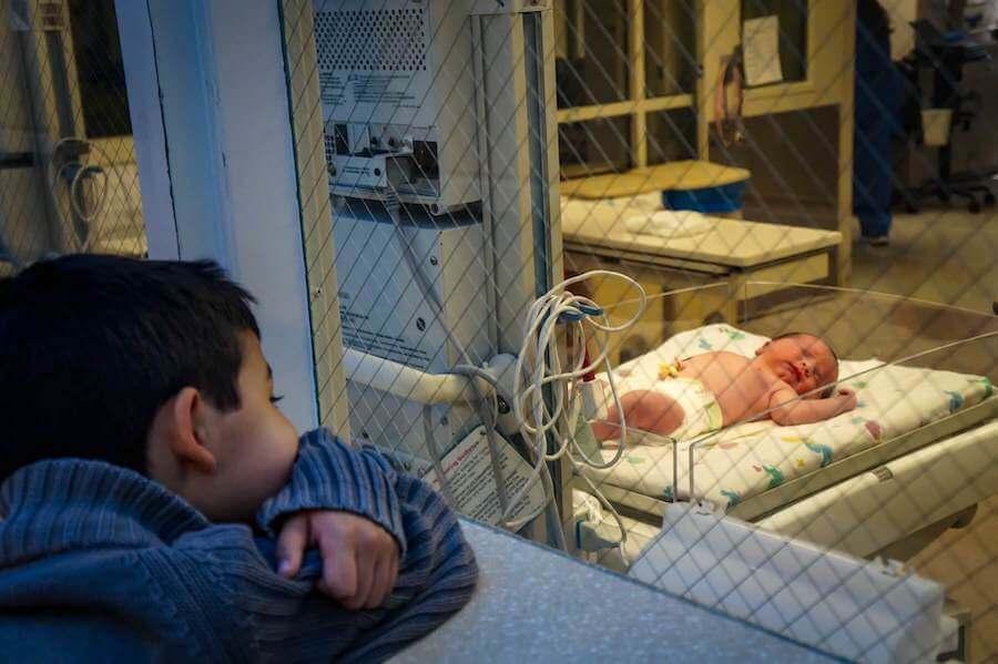 child looking through window at baby in hospital room nicu nursing