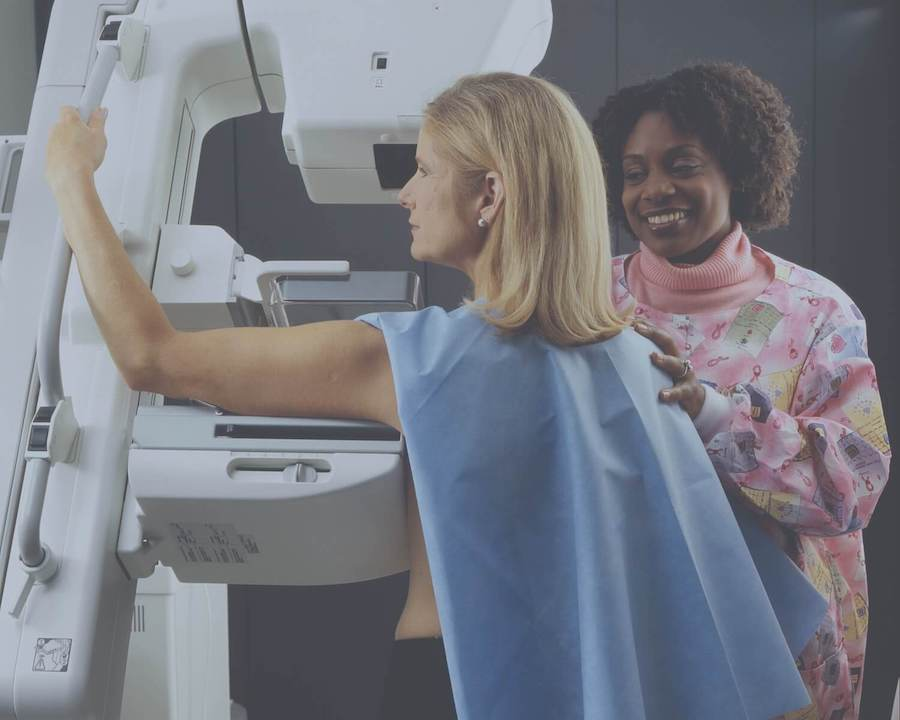 woman getting mammogram with nurse in background oncology nursing