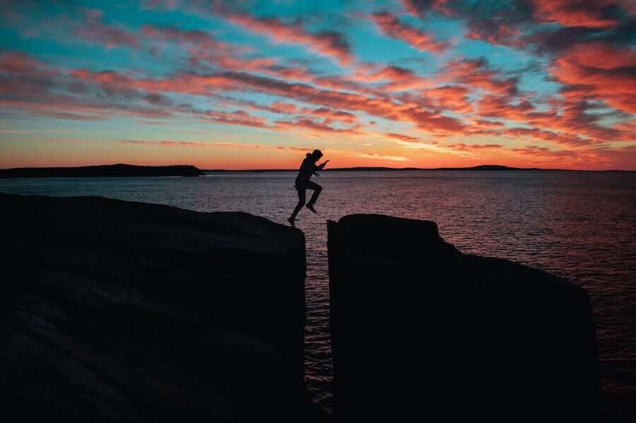man jumping between rocks in front of sunset hardest parts of being a travel nurse