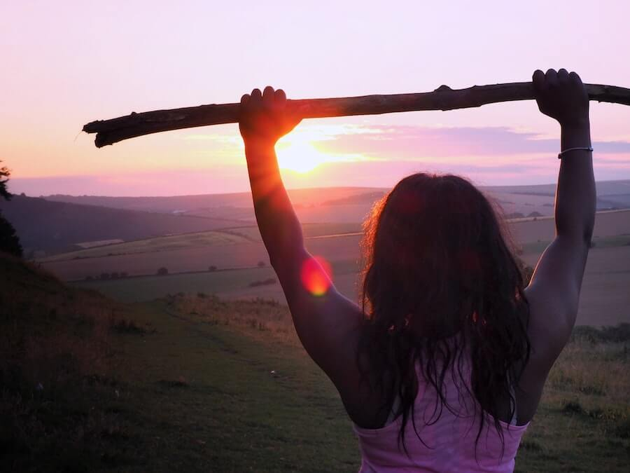 woman in front of landscape holding up stick athlete good habits hardest part of travel nursing