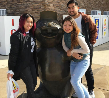 Kaithlyn with some friends by a statue.