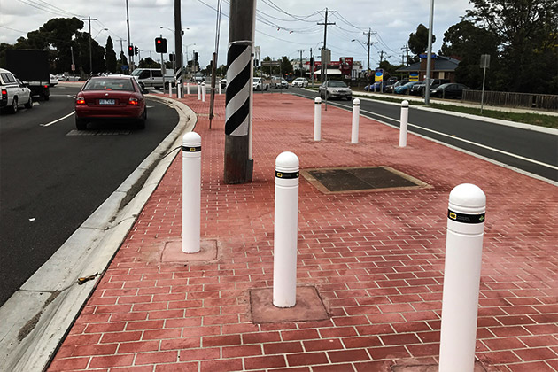 Energy absorbing bollards on road island