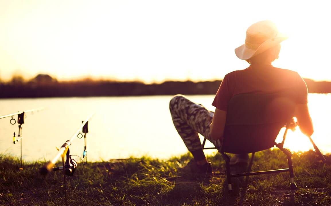 Young Man Fishing On Lake At Sunset Enjoying Manufactured Homes For Sale Houston