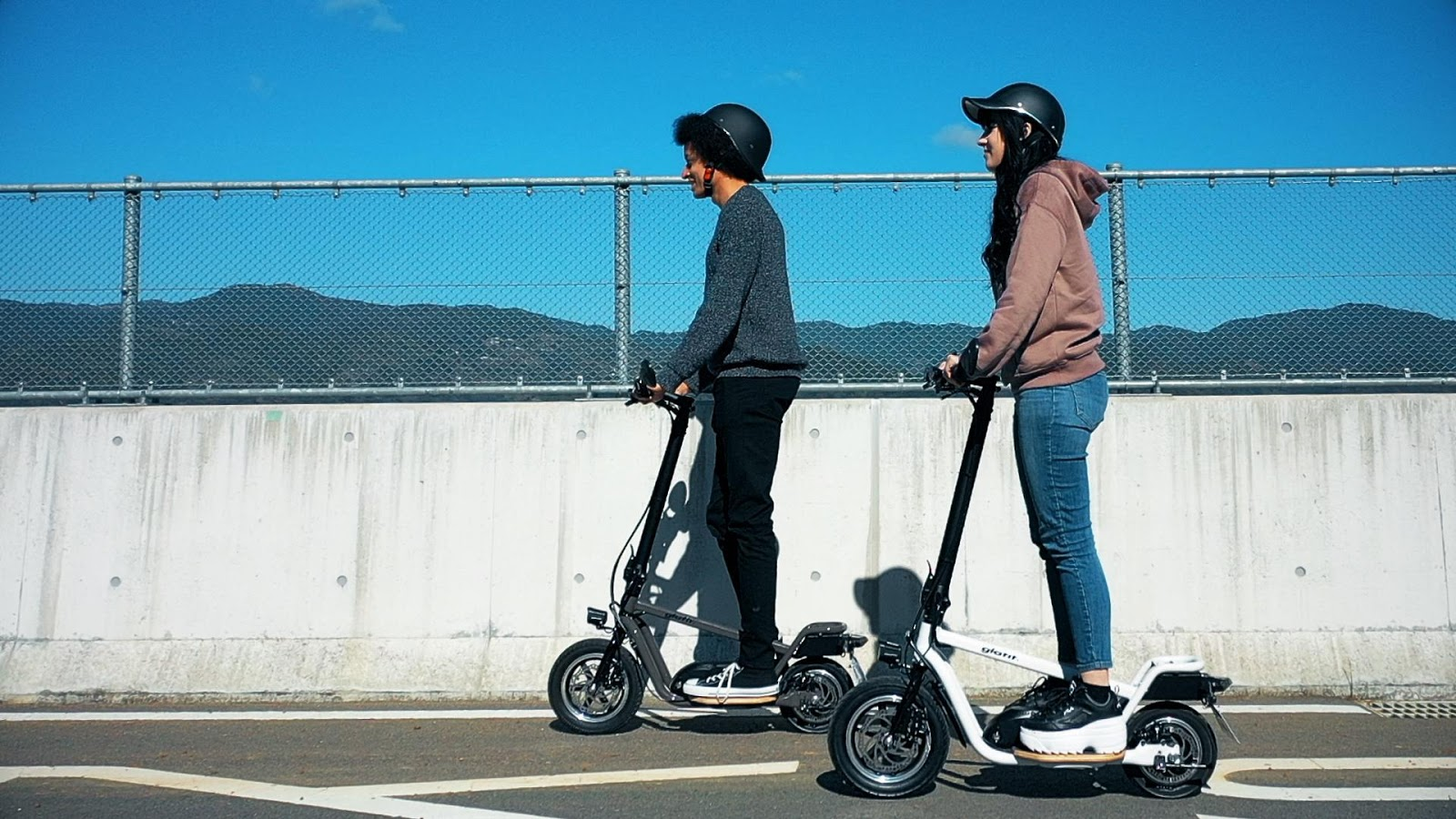 A couple riding e-scooters on the world; e-scooters are designed by Glafit