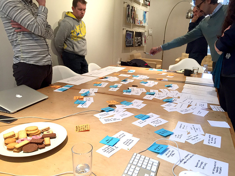 A card sorting workshop in progress. People stand around a table that's full of cards and post-it notes. Photograph.