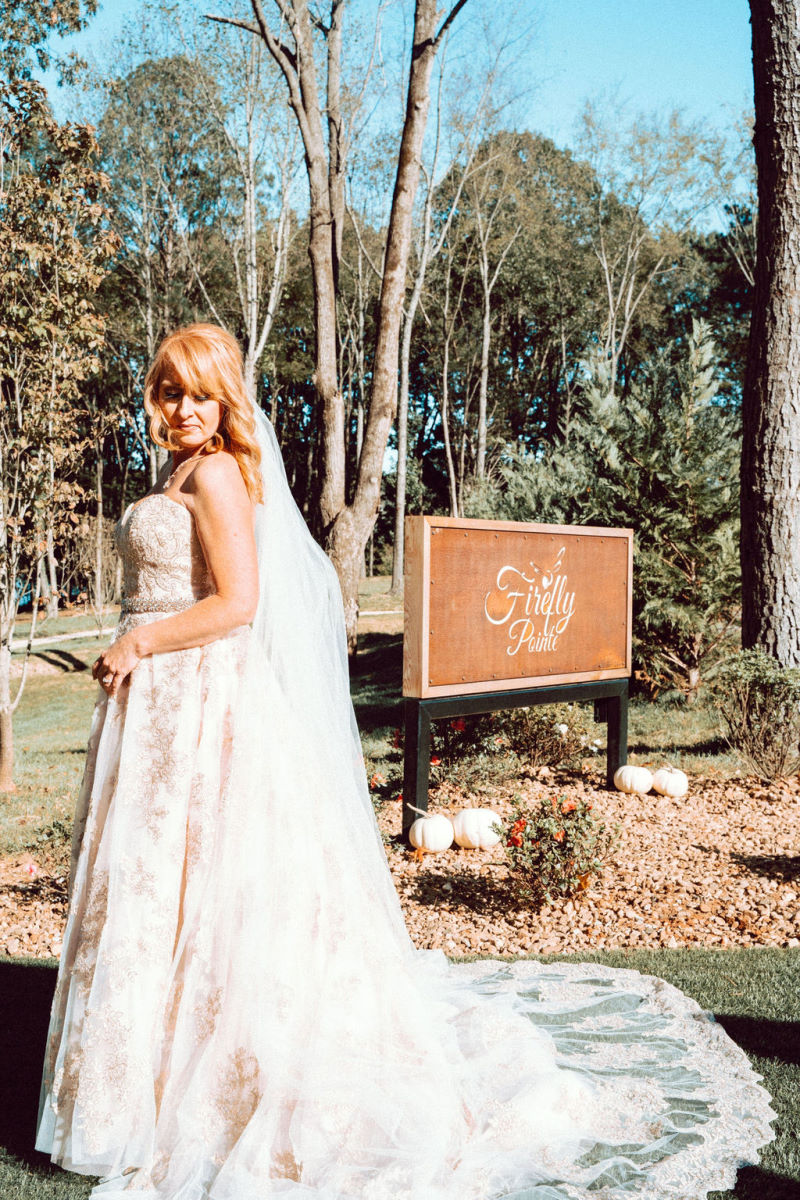 Bride in front of Firefly Pointe sign