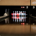 A bowling ball hits pins in a bowling alley in a leisure centre