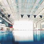 Light shines through large windows over a swimming pool in a leisure centre