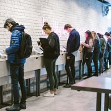 a group of people are ordering their food on tablets at a tossed QSR restaurant