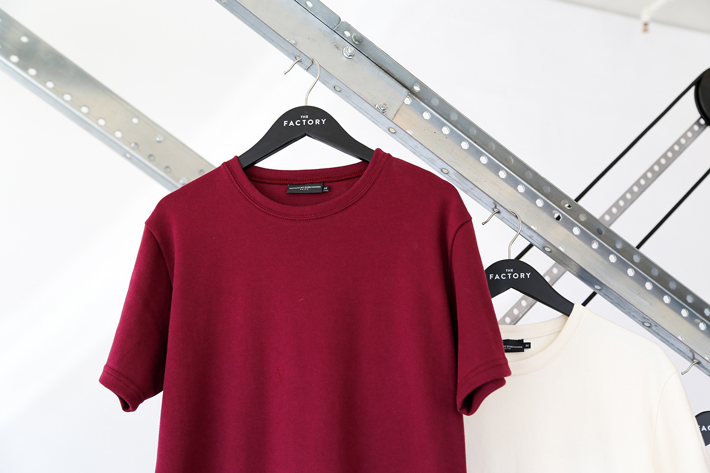 A Factory hanger holds a red T-shirt.
