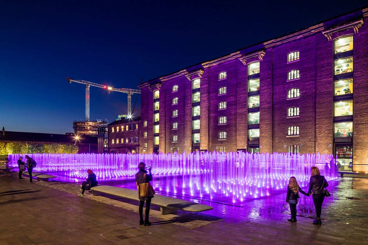 People looking at Granary Square fountains at night, lit up with purple LEDs