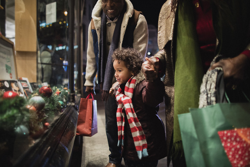 parents with their little boy looking at a window shop during Christmas
