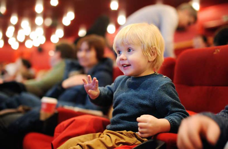 little boy at the theatre smiling