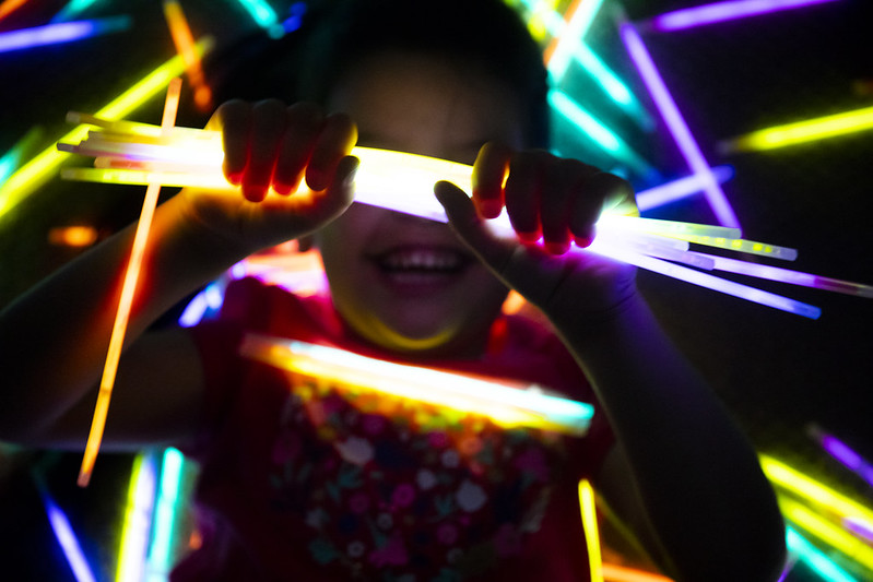 girl smiling as she hold glowsticks on her hands
