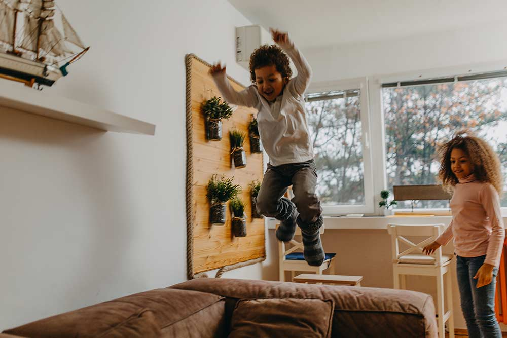 young boy jumping off couch while sister watches