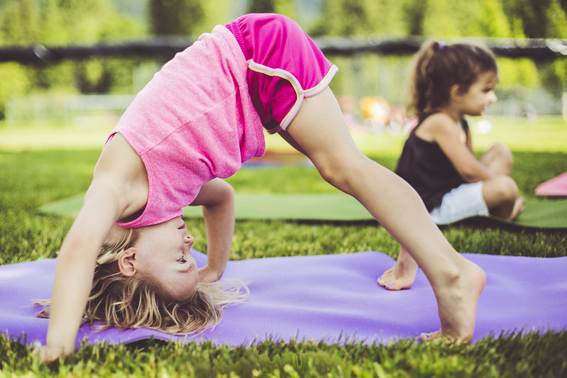 Girl in colourful pink clothes does yoga in the garden
