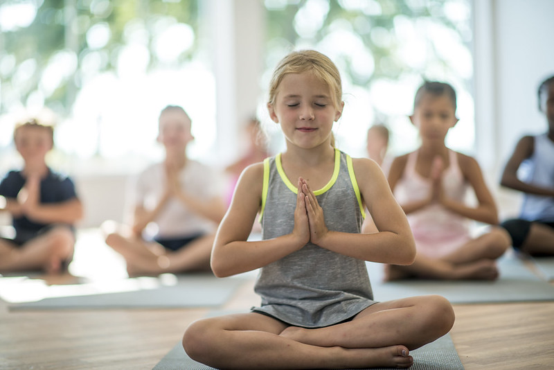 Child doing yoga during a well-being podcast