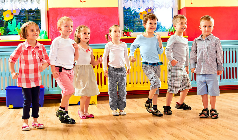 Group of children dancing together in a playroom in a nursery school.