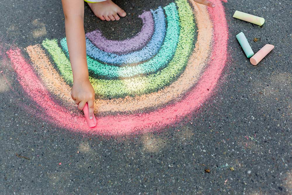 drawing a rainbow in chalk on the ground