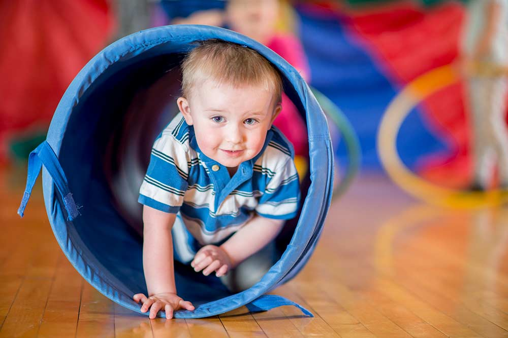 child in obstacle course tunnel