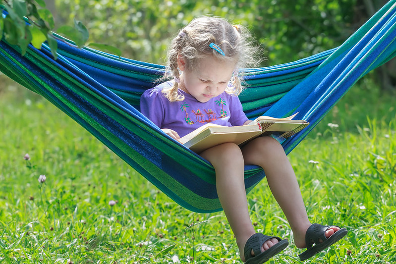 Child reading outside in a hammock