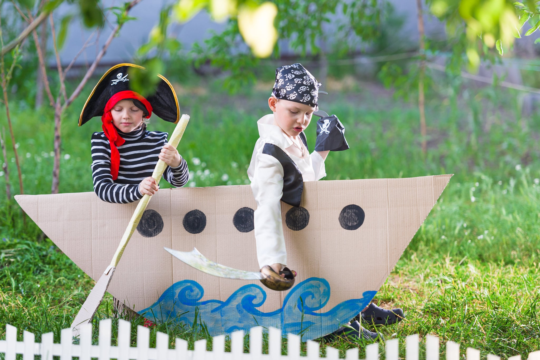 two boys playing in makeshift pirate ship