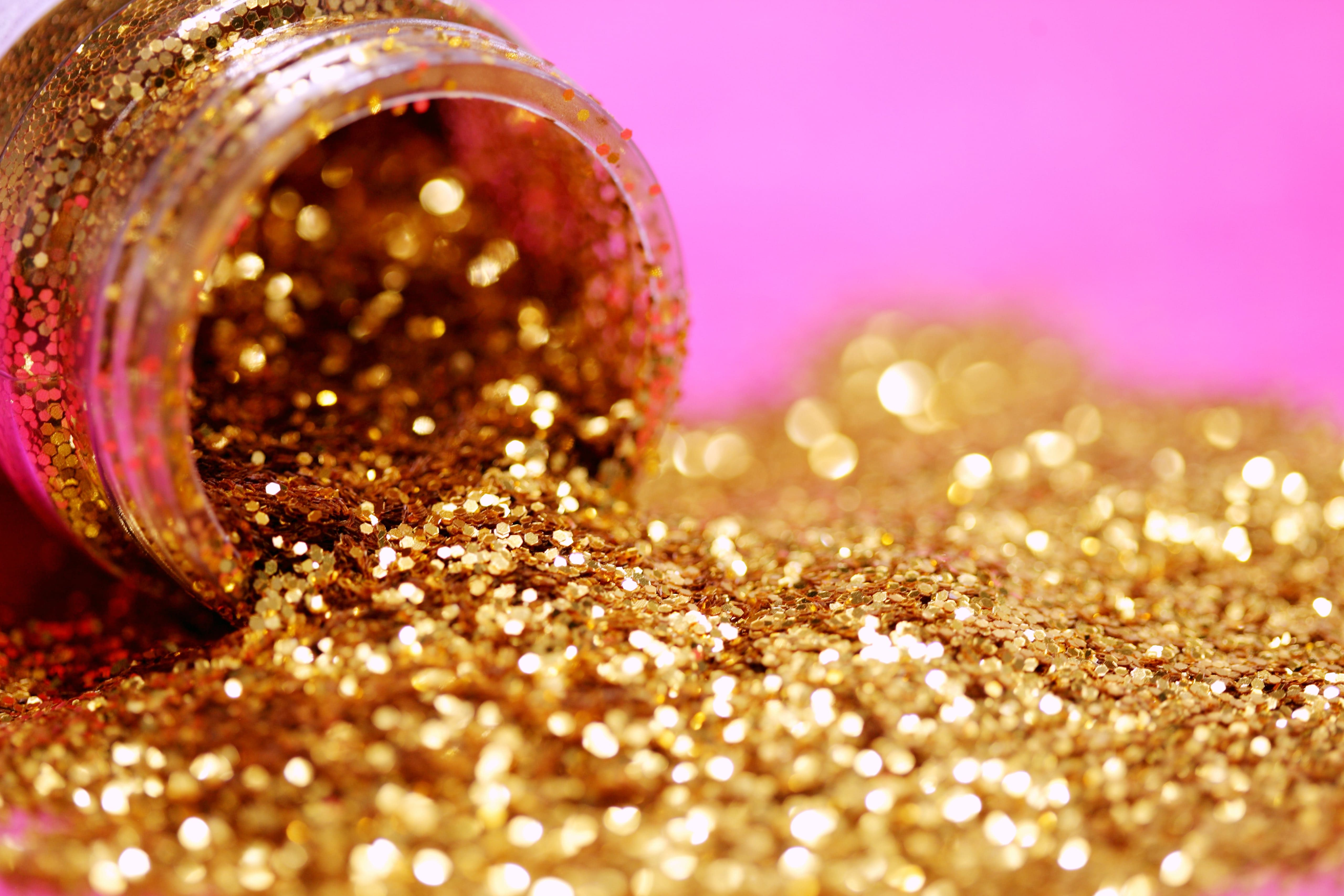 gold glitter spilling out of tub onto pink background