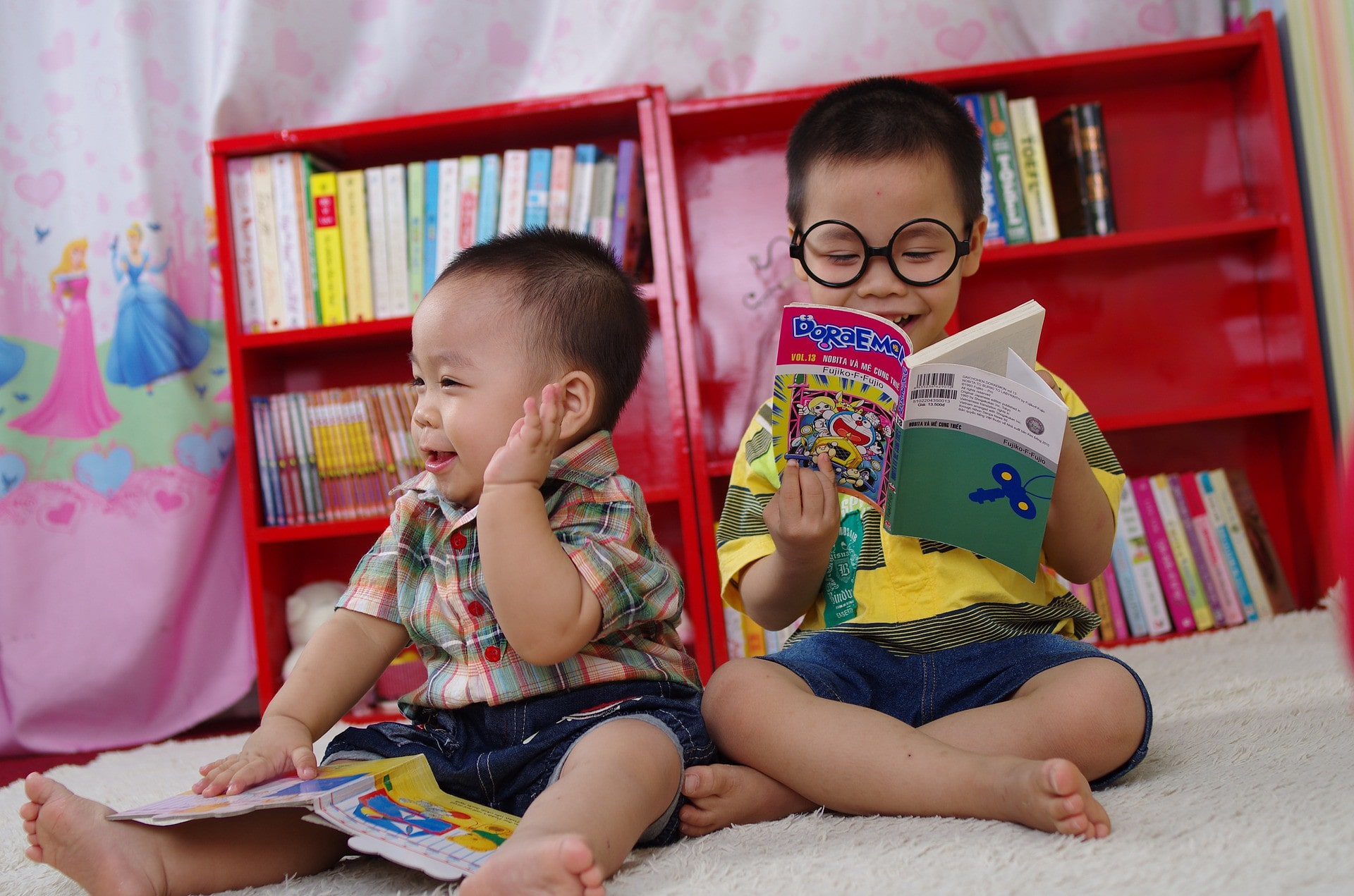 two brothers sat on floor reading
