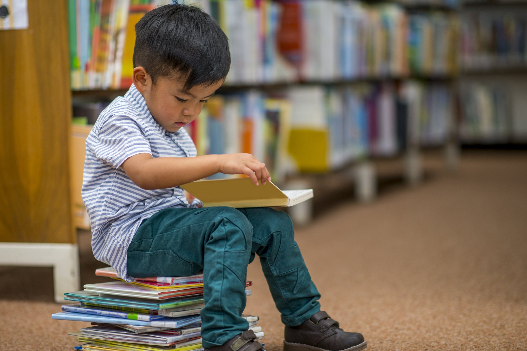 young boy sat on stack of books in library