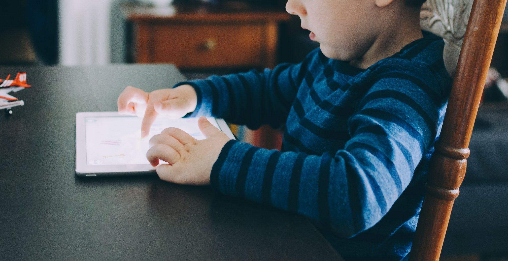 young boy sat at table playing on tablet