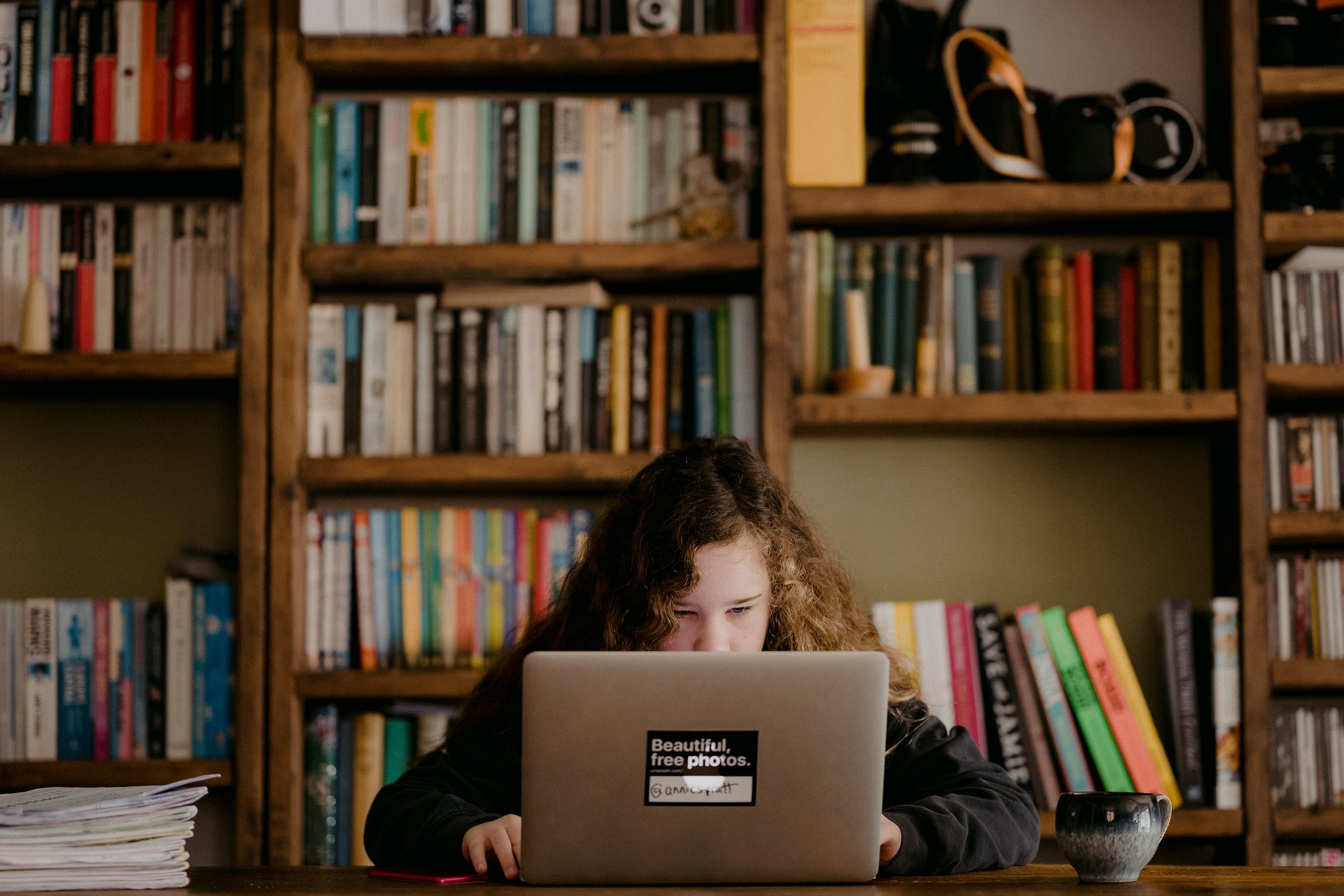 young girl at laptop surrounded by bookshelves