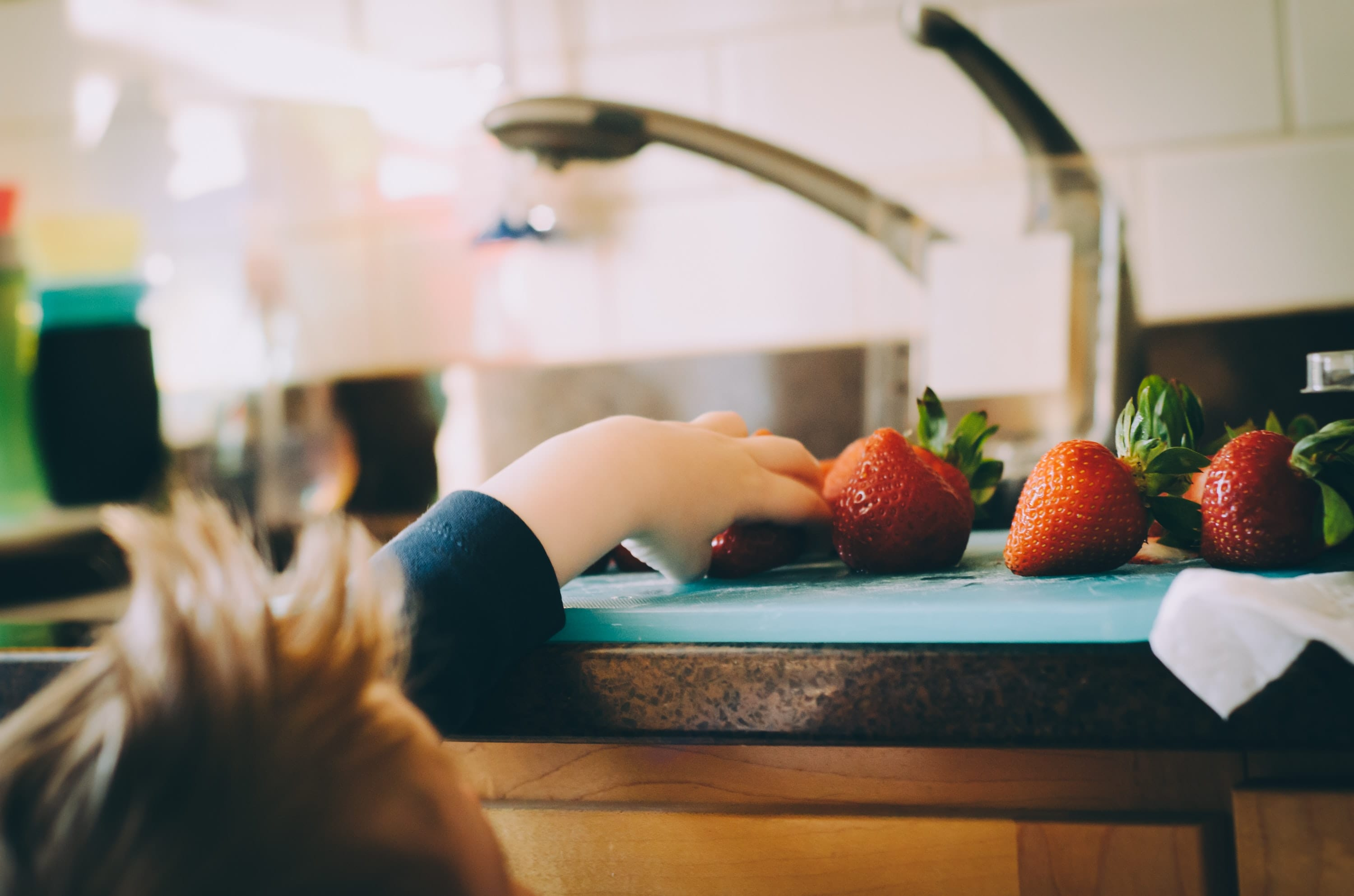 child's hand grabbing a strawberry from the kitchen counter