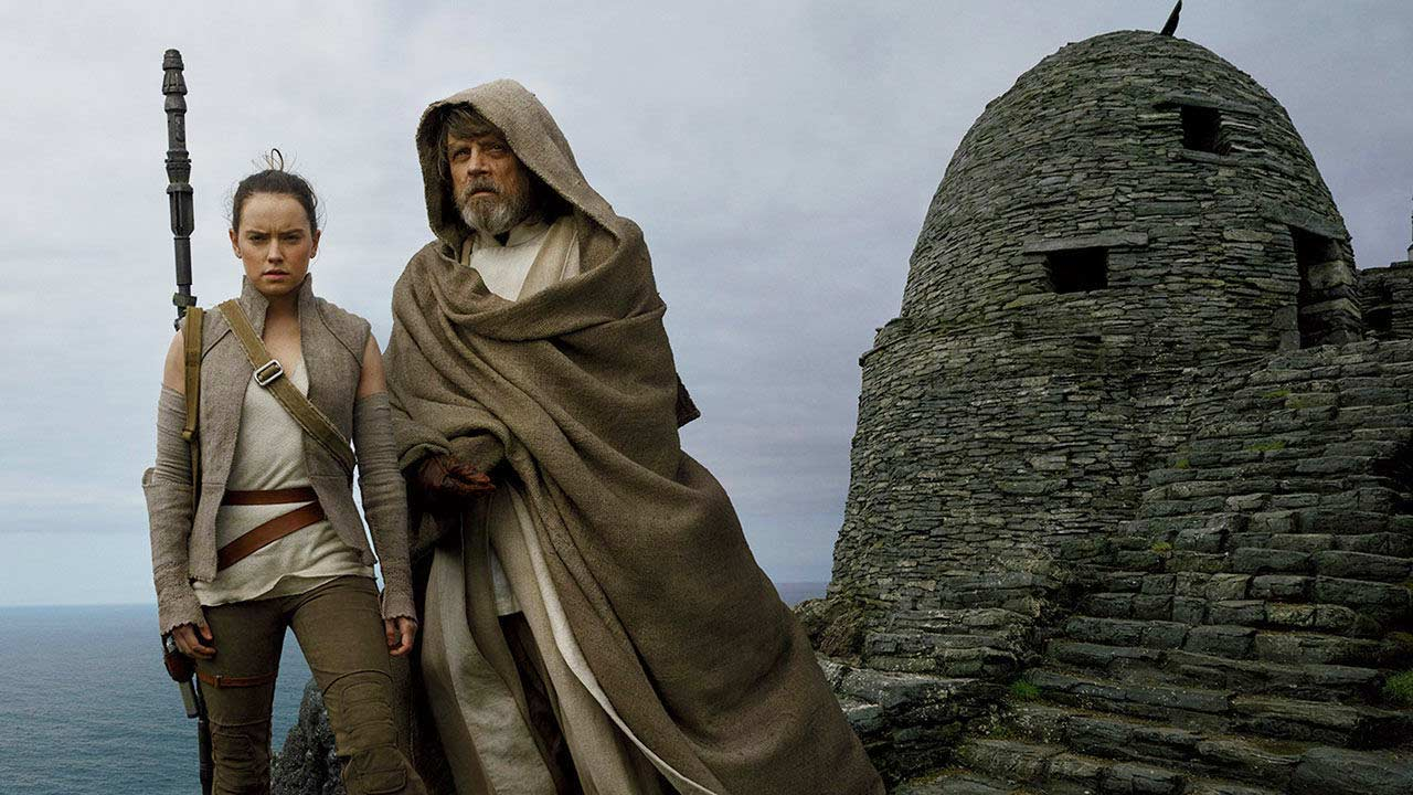 Rey and Luke Skywalker stand together on a clifftop