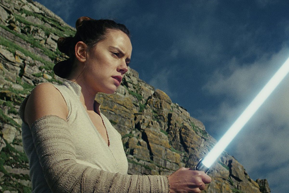 Rey stood with lightsaber on clifftop