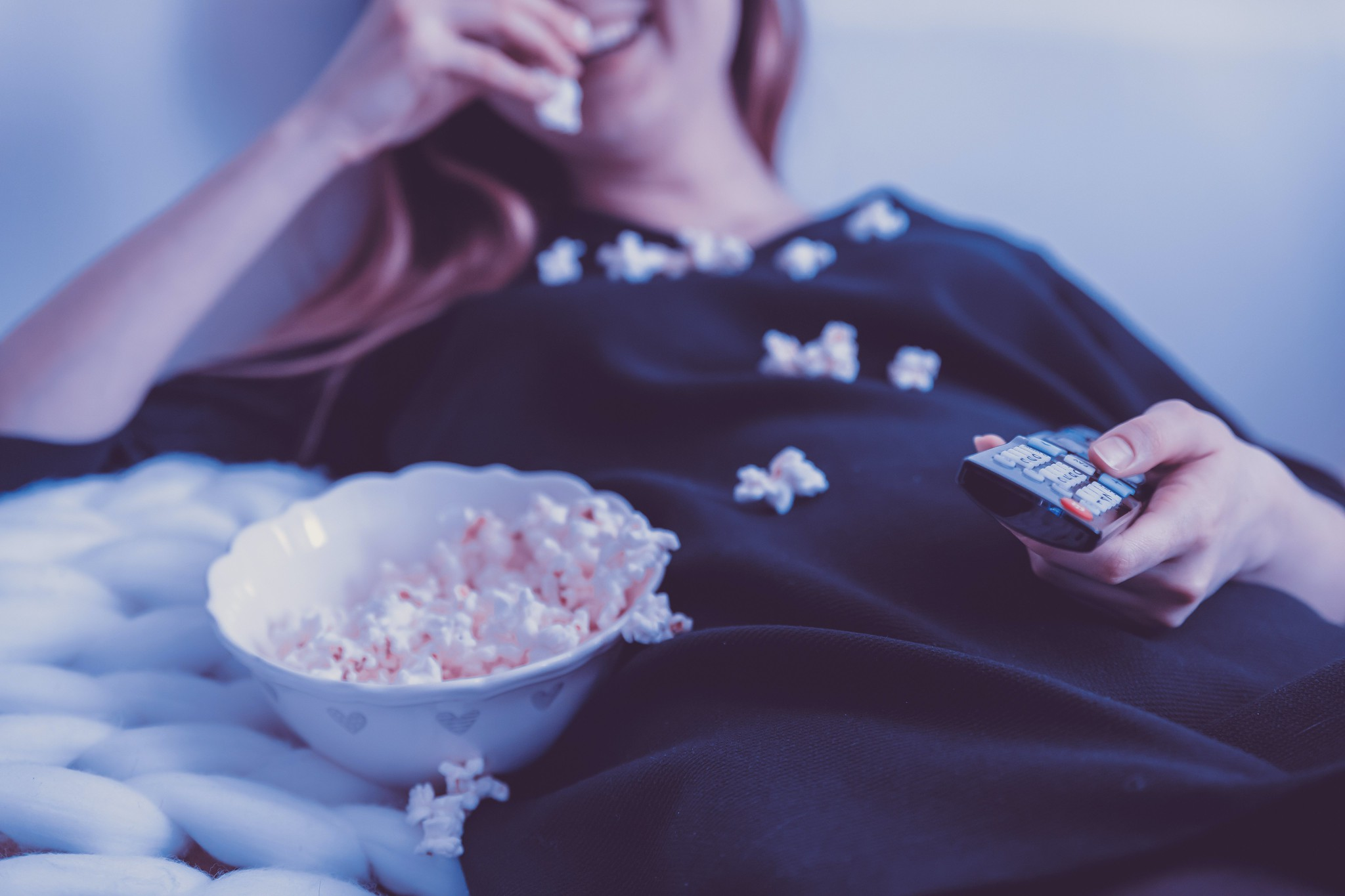 young woman eating popcorn watching a film