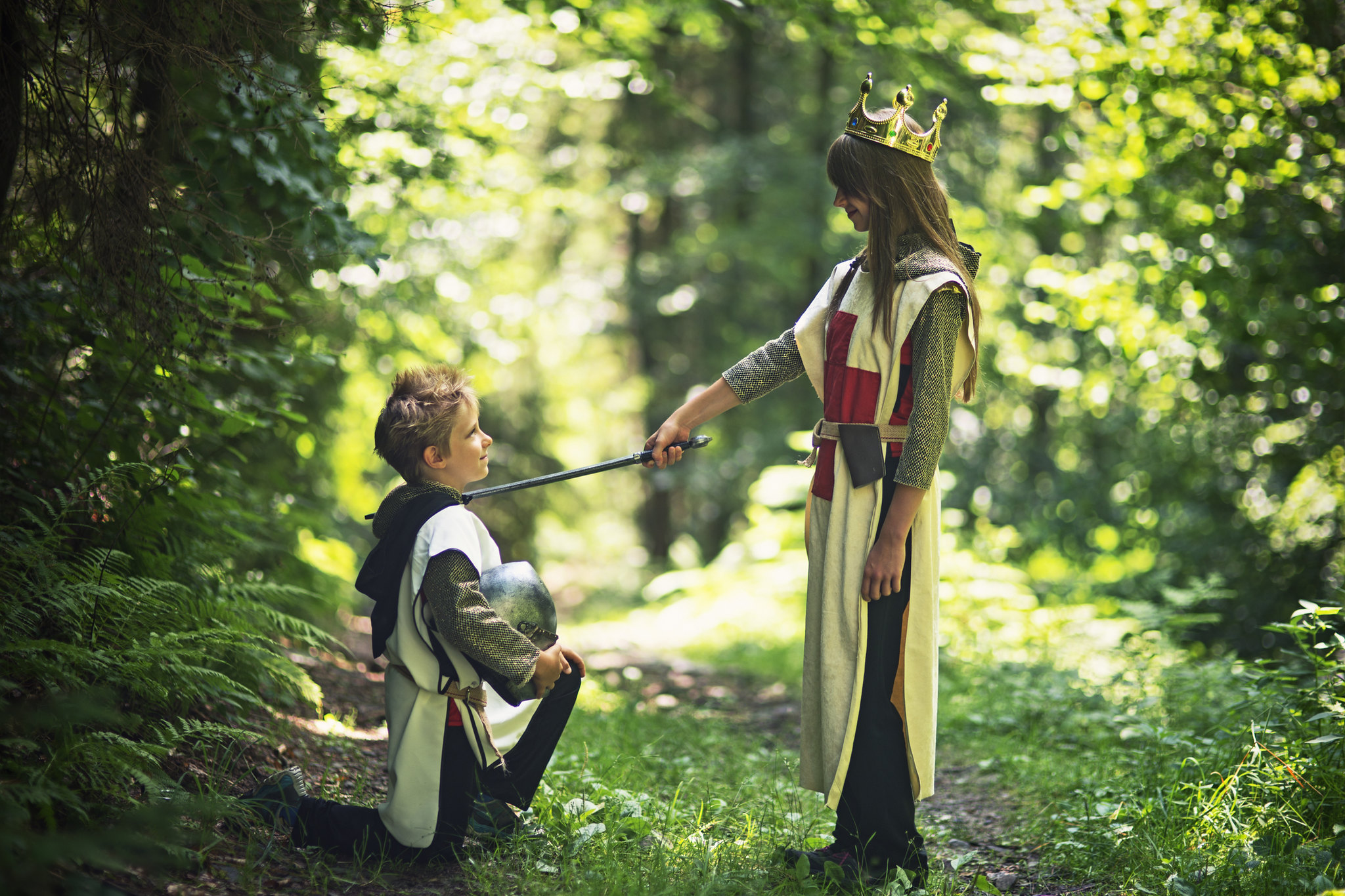 boy and girl dressed as knights in the forest