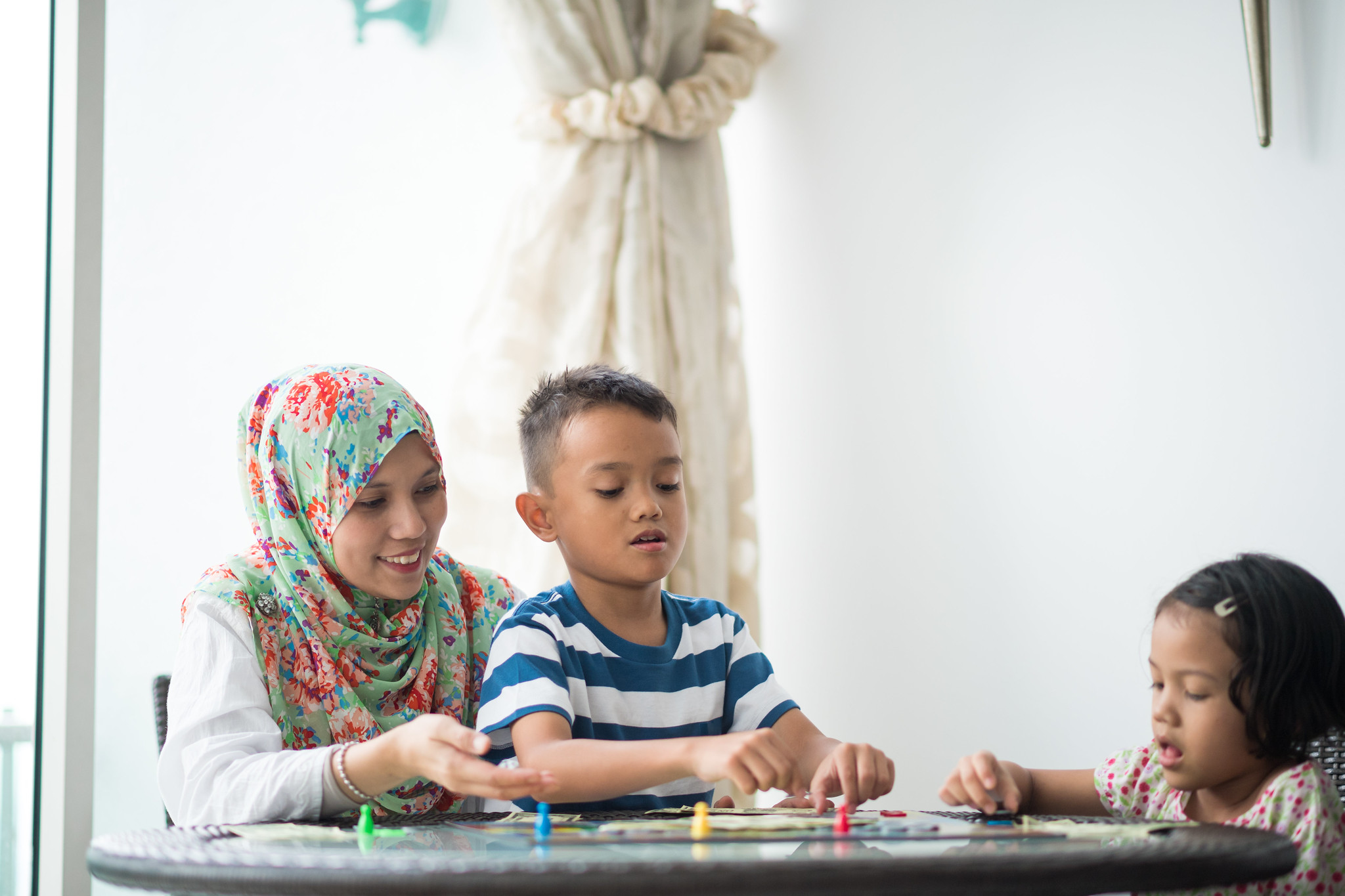 mother playing board game with son and daughter